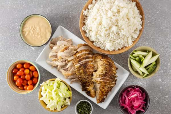 Sliced rotisserie chicken on a platter with rice bowl