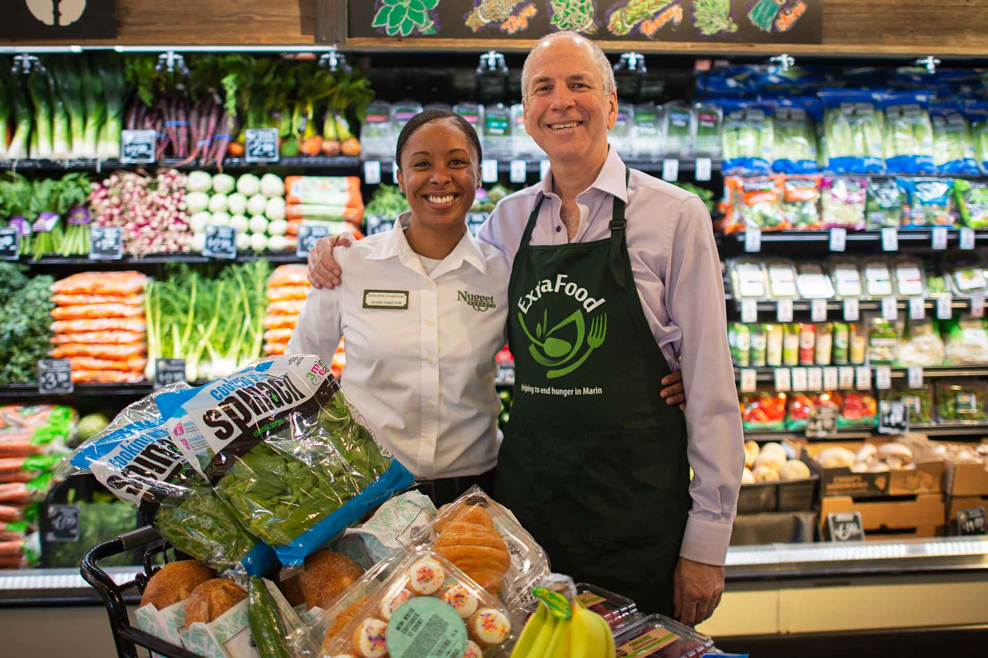 Nugget Markets' store director poses with Extra Food program representative