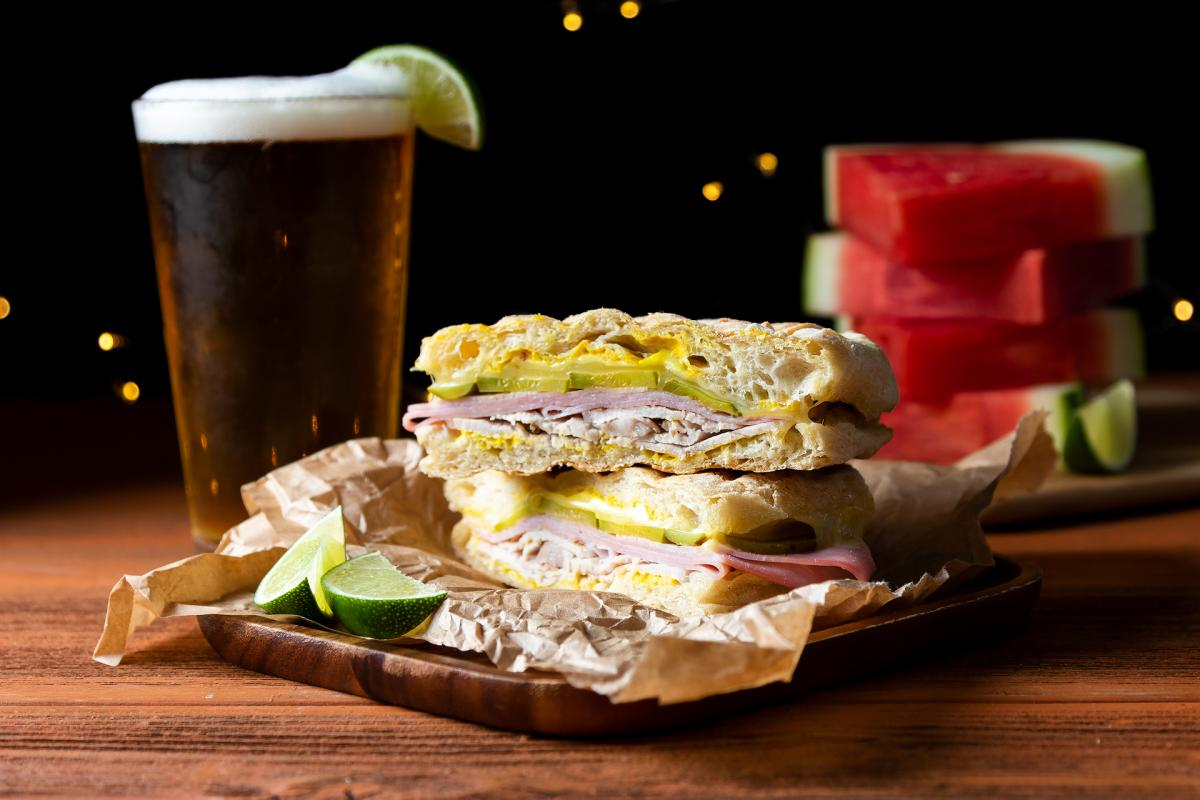 cubano sandwich on a plate, glass of beer, watermelon slices in the background