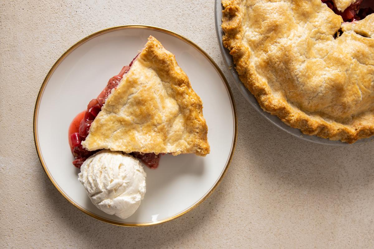 strawberry rhubarb pie slice with ice cream and rest of pie
