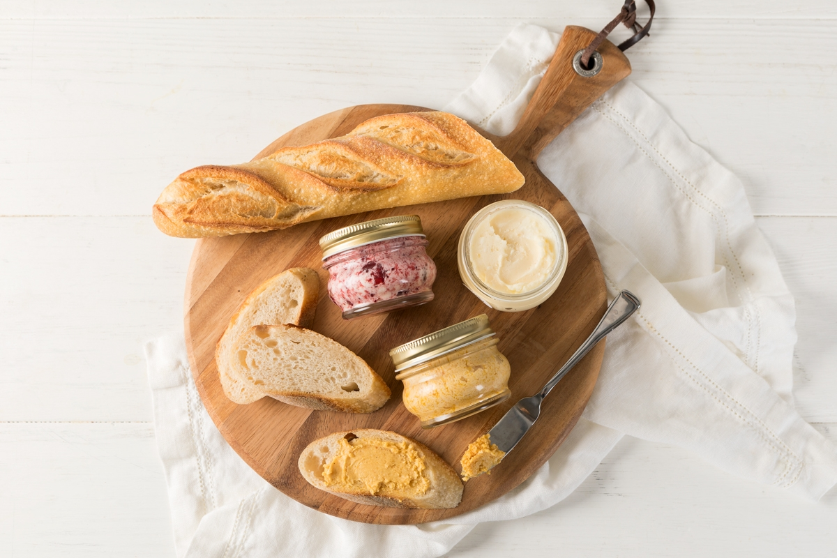three whipped butters in jars with bread on a cutting board